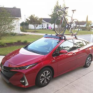 2017 Toyota Prius Prime (Hypersonic Red) with bicycle on roof